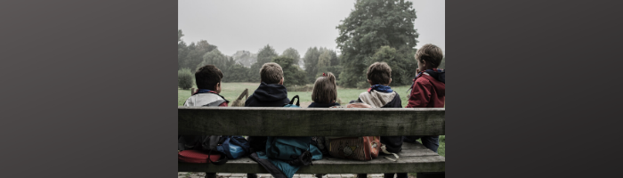 Children on a bench looking at a park