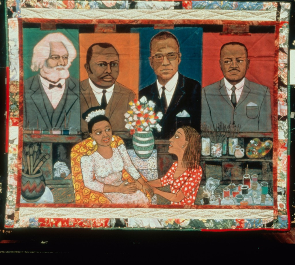 Quilt with image of two women with paints in front of portraits of four figures from Black history (Frederick Douglass, Malcolm X, and others)