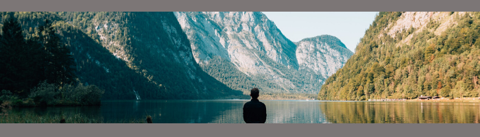 Person meditating in natural landscape of lake and mountains