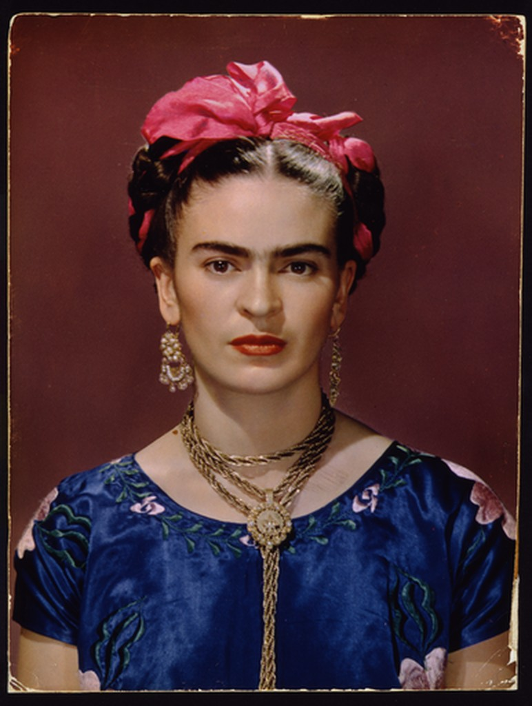 Portrait of Frida Kahlo in a blue embroidered dress with Jewelry and a pink ribbon braided into her hair