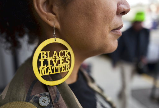 A woman pictured in profile wearing a large Black Lives Matter earring