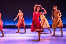 Dancing women in colorful dresses