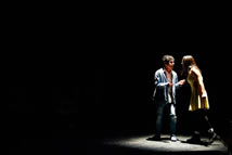 Man and woman onstage under a spotlight