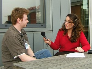 A woman holding  a microphone and interviewing a man.