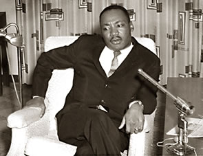 Martin Luther Kings Jr. sitting at microphone.