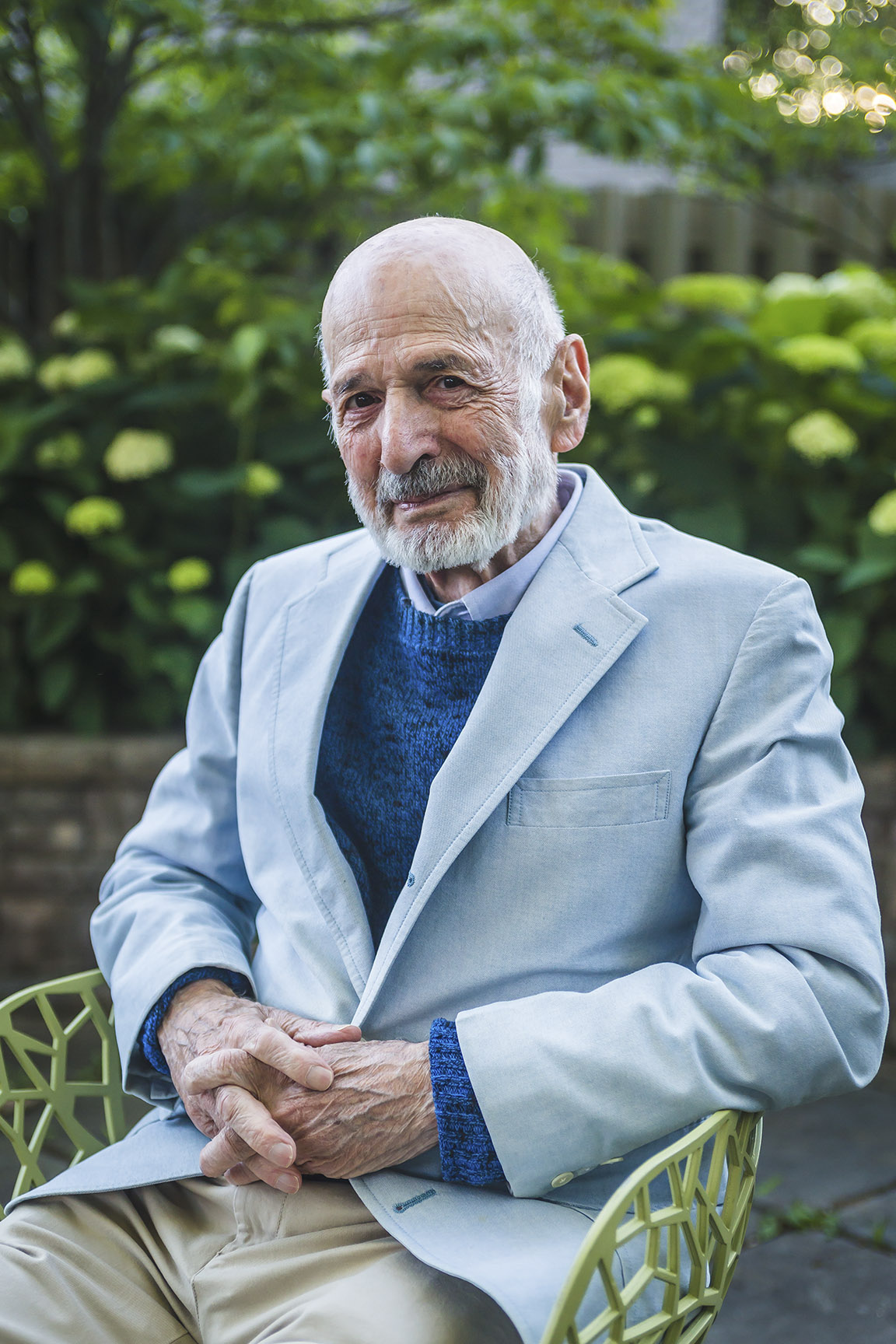 Elderly man in light blue jacket seated in a garden.