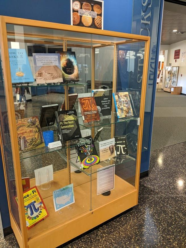 Photo of exhibit case with books on pi (the numerical constant)