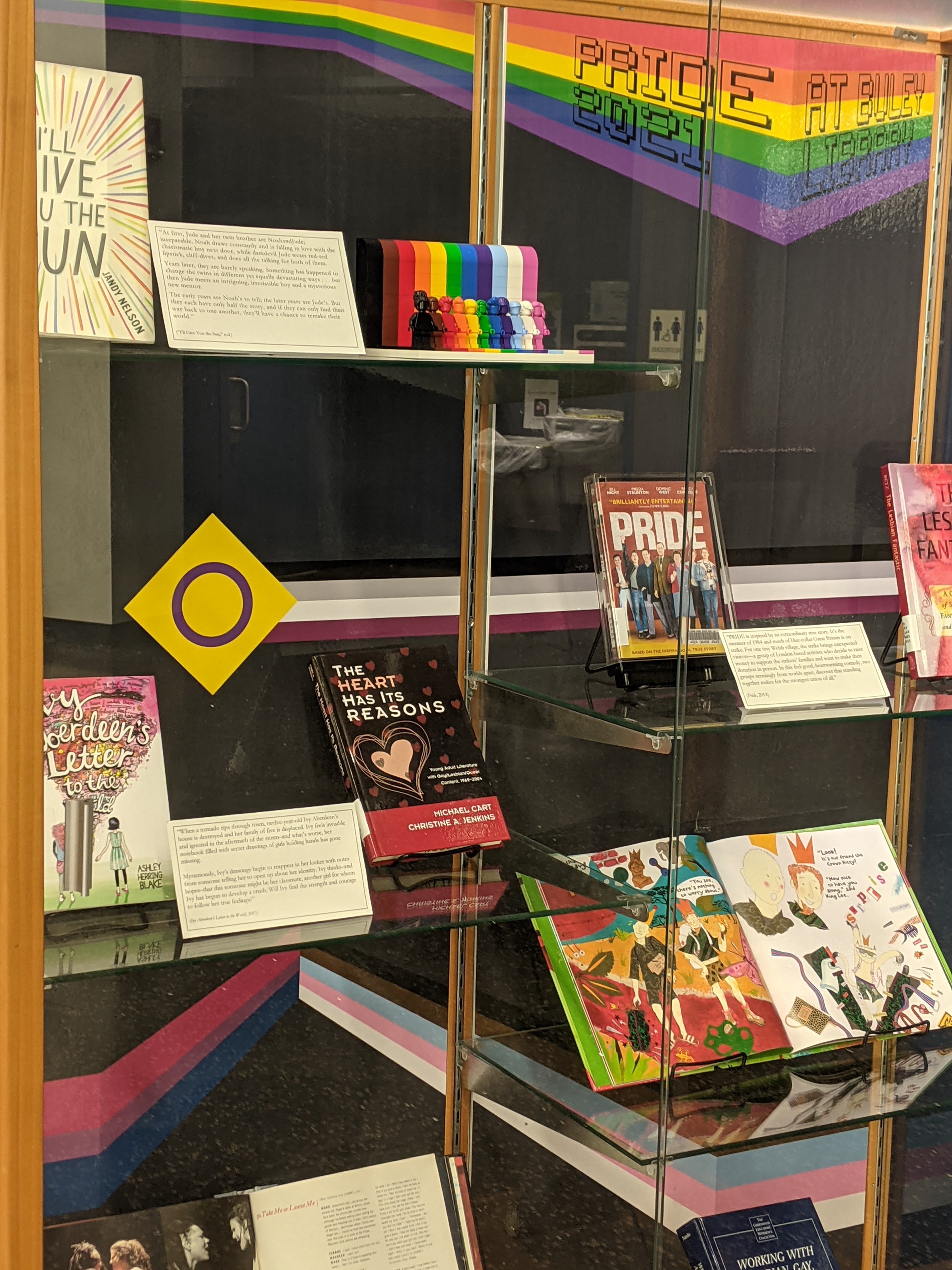 """Photo of Pride Month exhibit case with banner, books, and Lego """"Everyone is Awesome"""""""