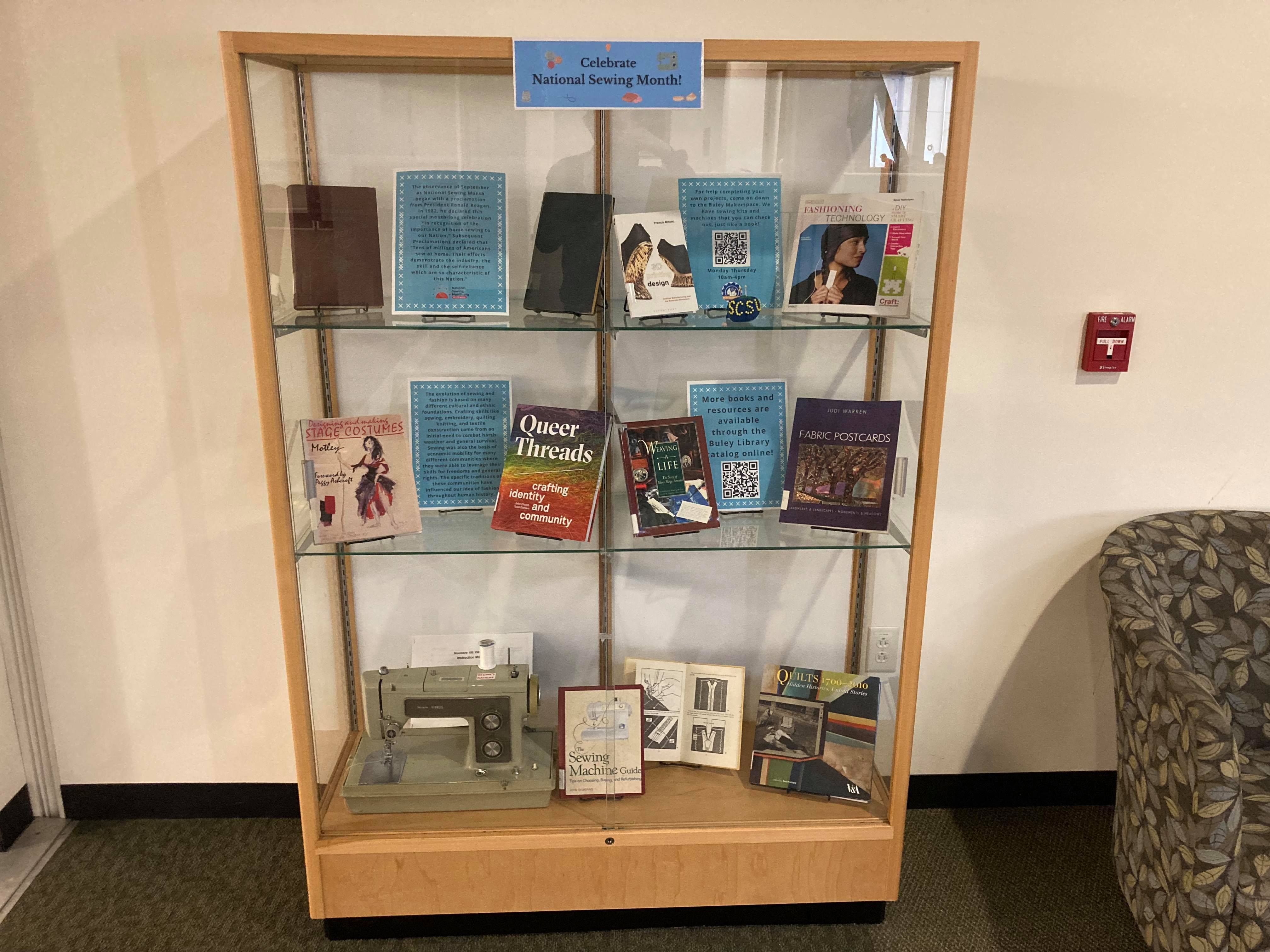 Entire exhibit case with books on sewing and fashion and a vintage sewing machine