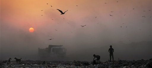 Image of young ragpickers searching for reusable material at a garbage dump in New Delhi, India.