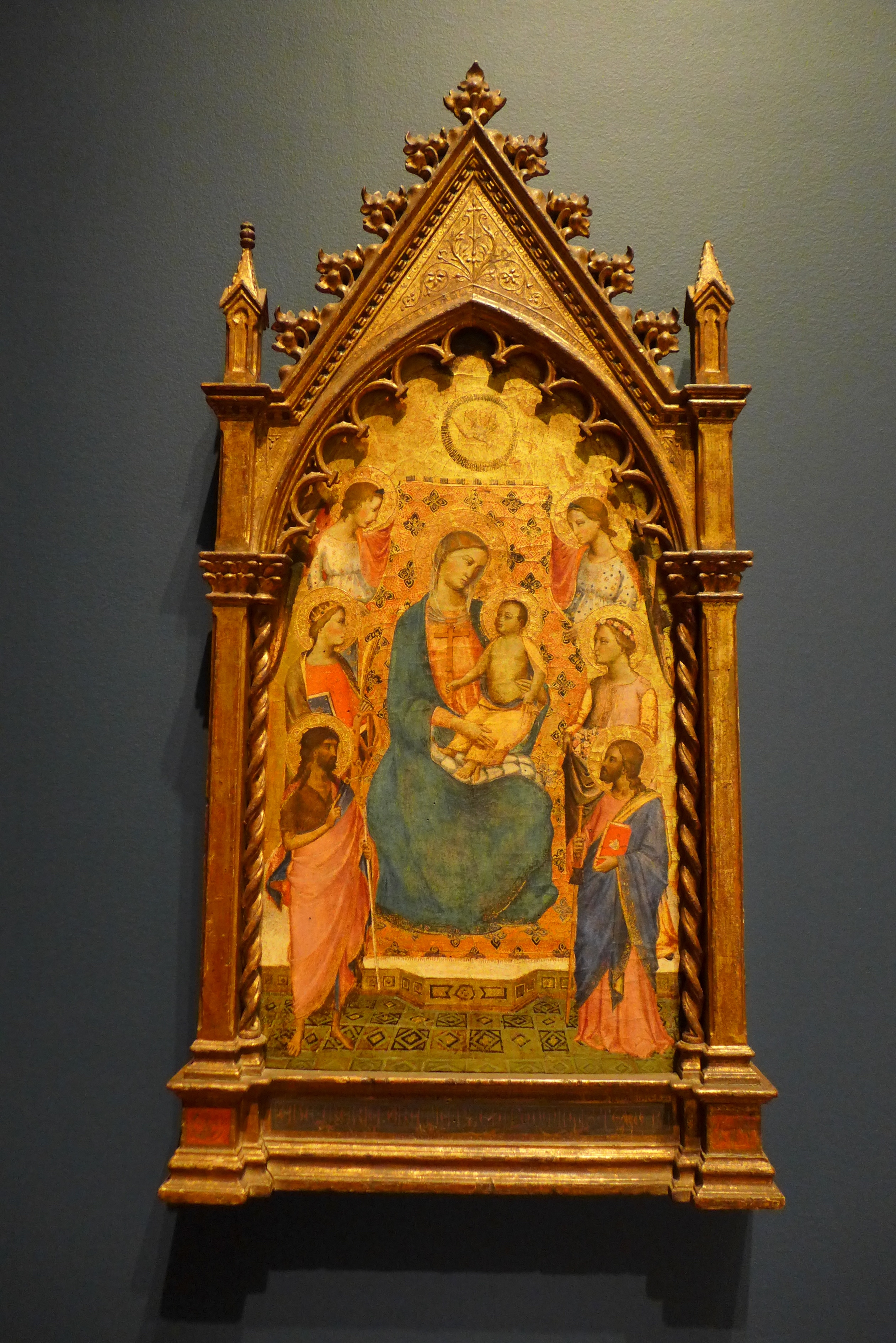 Mary and Christ sit on a throne in front of a flat gold ground. Angels and saints stand around them. The picture has the shape of a pointed arch.