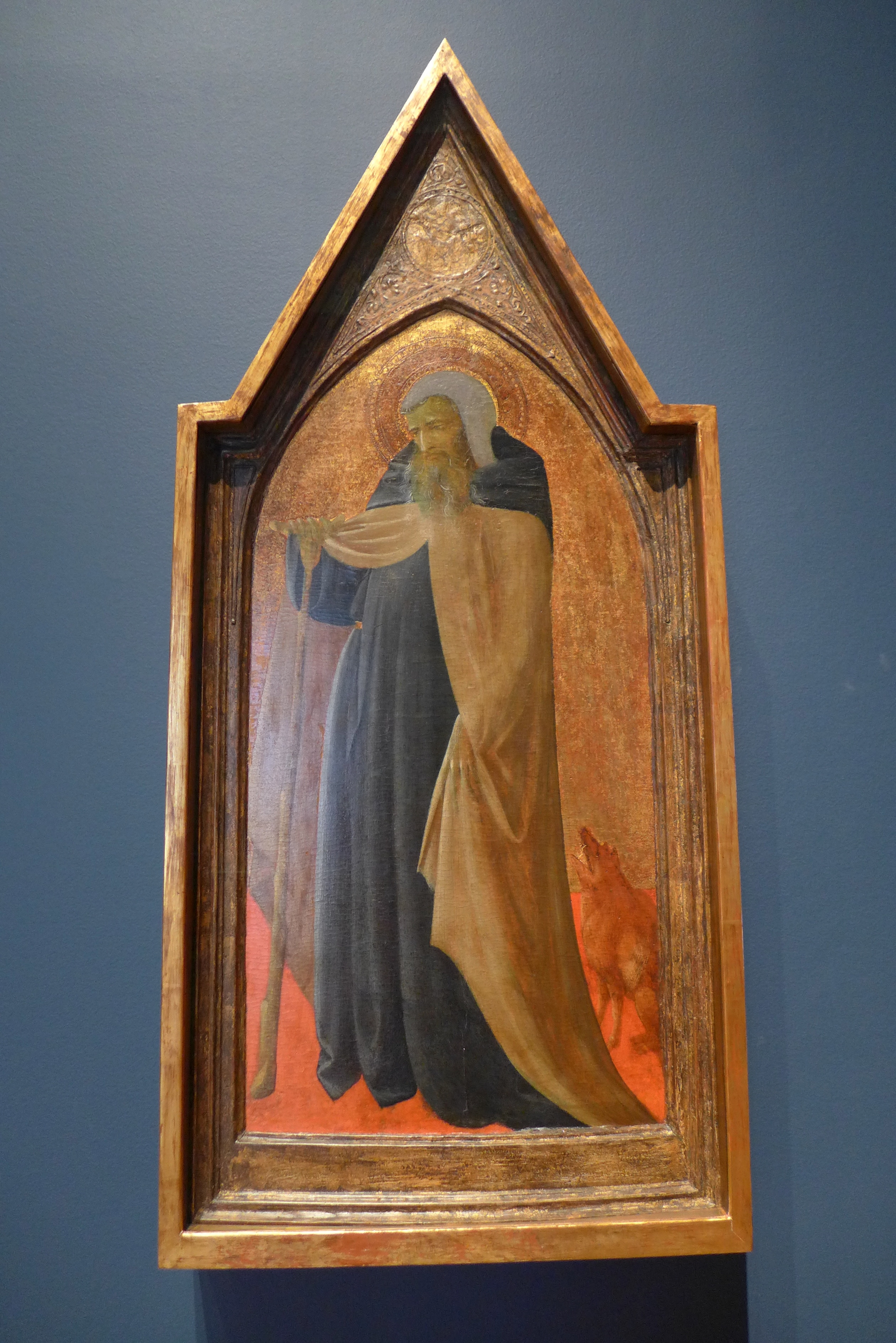 Saint Anthony turns towards his right. The shape of the painting is a pointed arch.