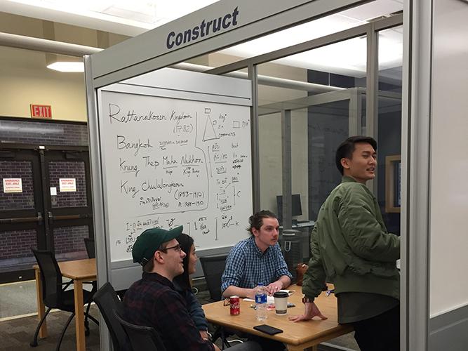 3 men writing on whiteboard