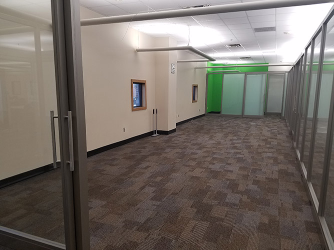 empty floor and walls with green wall in distance