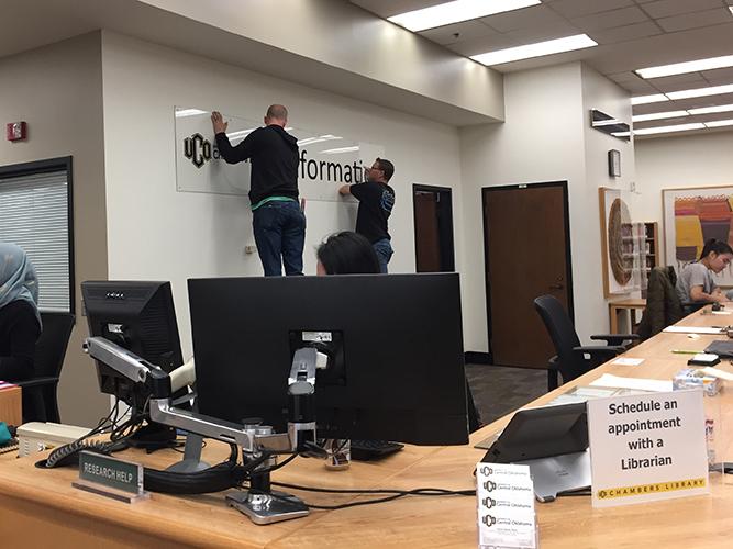 desk with men installing sign