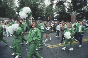 a color photograph of a homecoming parade with cheerleaders in green tracksuits and pompoms marching in the foreground