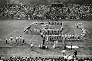 black and white photo of the Marching 100 standing in an arrangement that spells