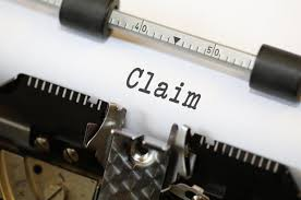 "Paper in typewriter with word ""claim"""