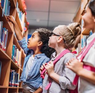 three children getting a book off a shelf