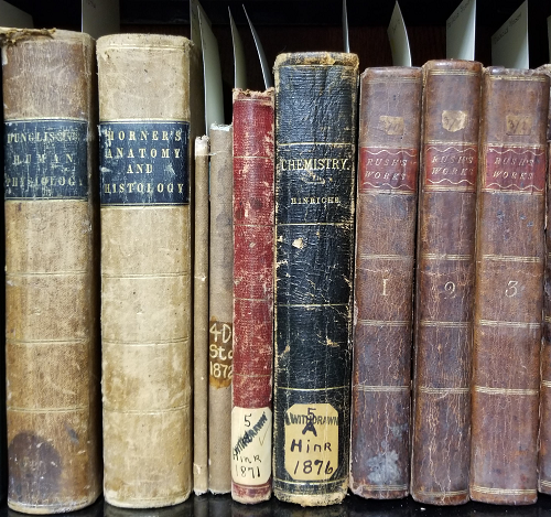 "A row of old books including ""Horner's Anatomy and Histology"", ""Chemistry"", and ""Rush's Works"" volumes 1-3."