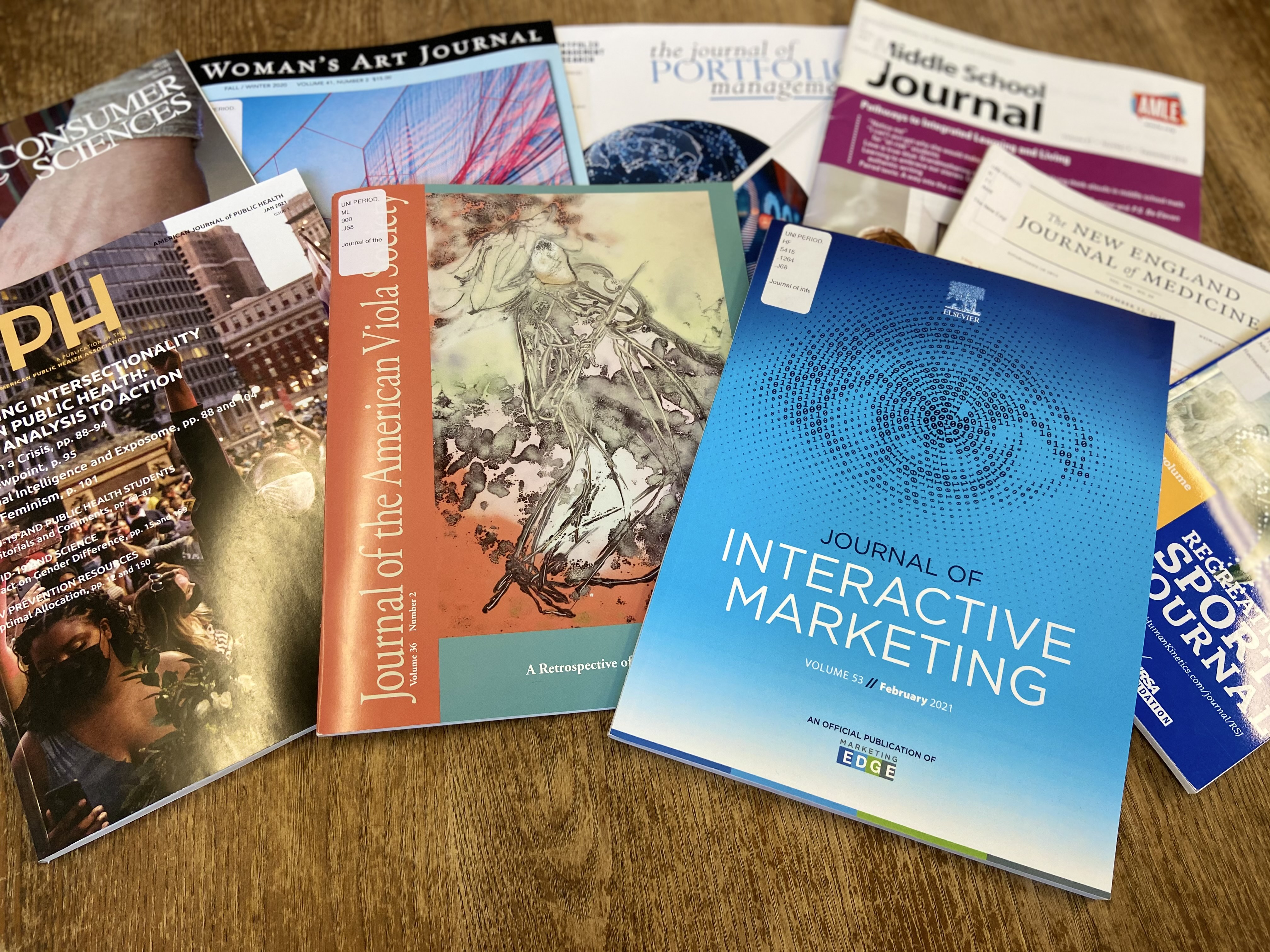 A mix of scholarly journals on a table, including the journal of interactive marketing