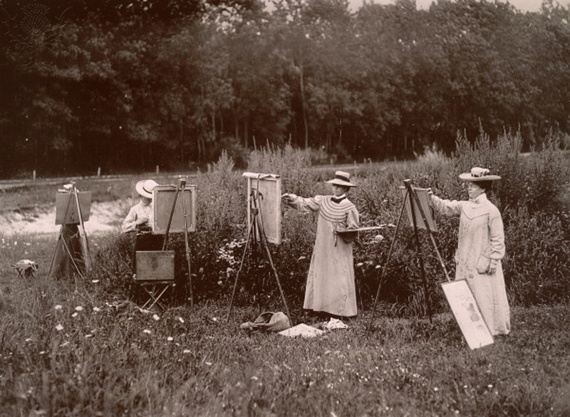 Four women painting in a field