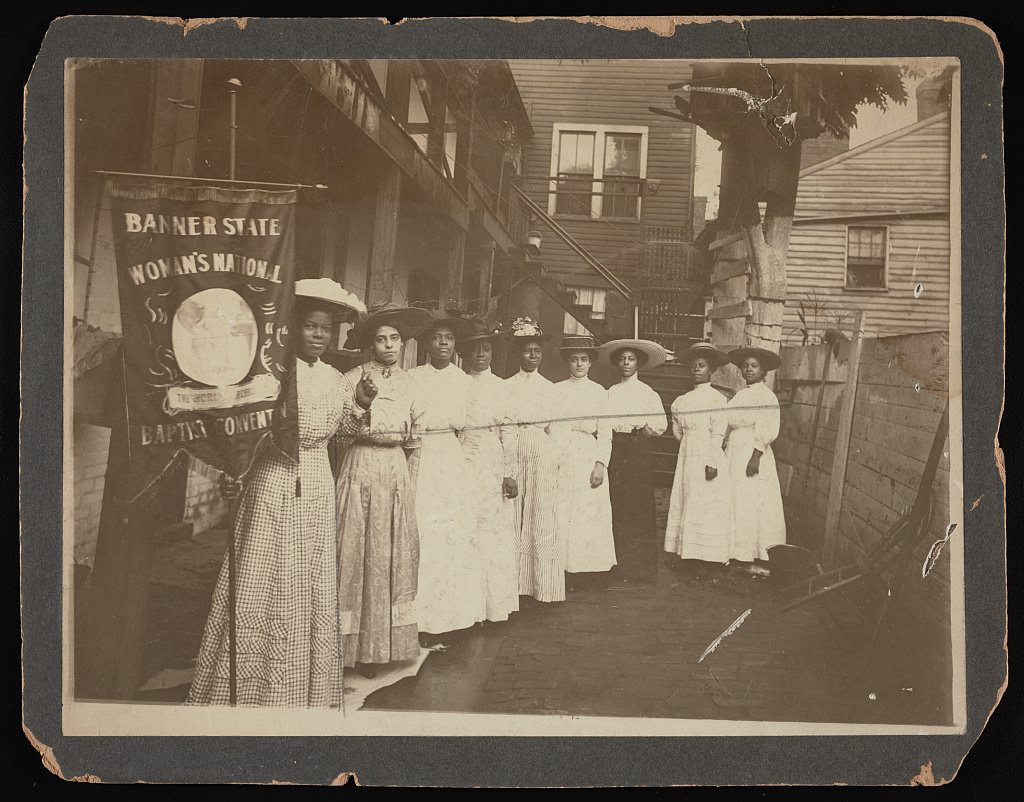 """Nine African-American women posed, standing, full length, with Nannie Burroughs holding banner reading, 'Banner State Woman's National Baptist Convention'"" Library of Congress."