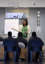 Woman speaking to several boys in a youth prison.