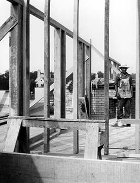 Graycliff frame and chimney under construction showing a workman