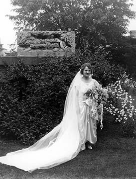 Dorothy Martin Foster posed in the garden by the Bock sculpture wearing her wedding dress