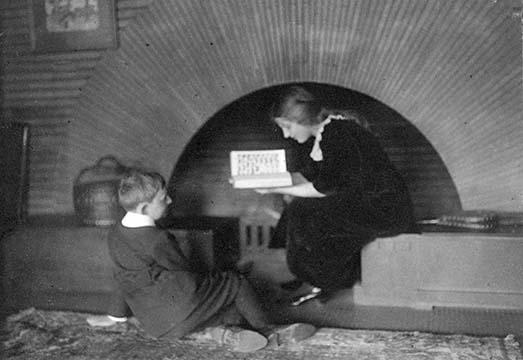 Dorothy Martin sitting next to the sunburst fireplace reading to Darwin R. Martin, circa 1912