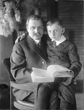 Darwin D. and Darwin R. Martin seated in a barrel chair in the Martin House library, 1912