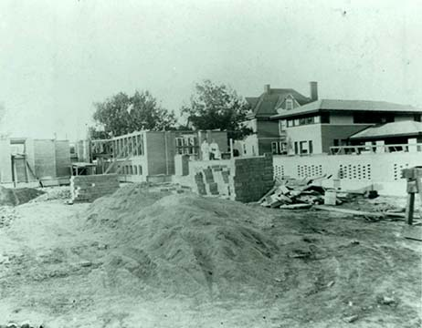 Exterior view of the pergola and conservatory under construction with the Barton House in the background, 1904