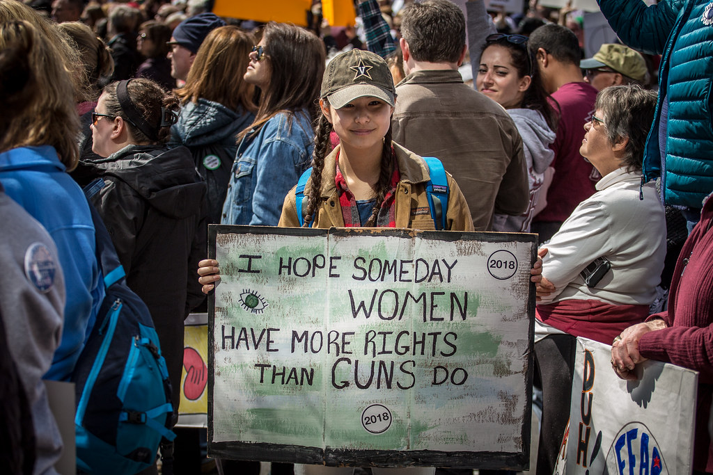 Young woman holds a gun control sign