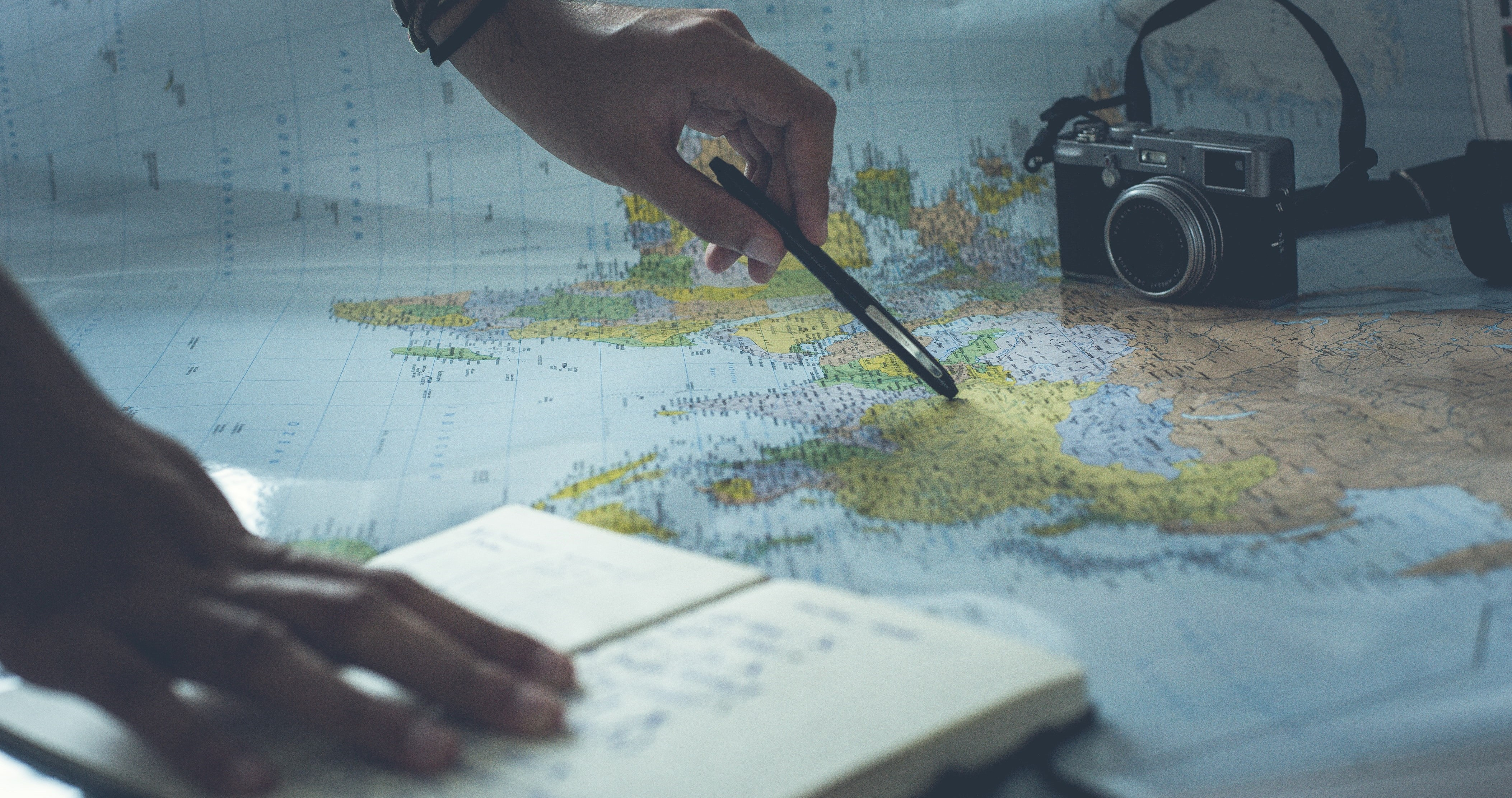 A Map of the world with hands holding a pen.