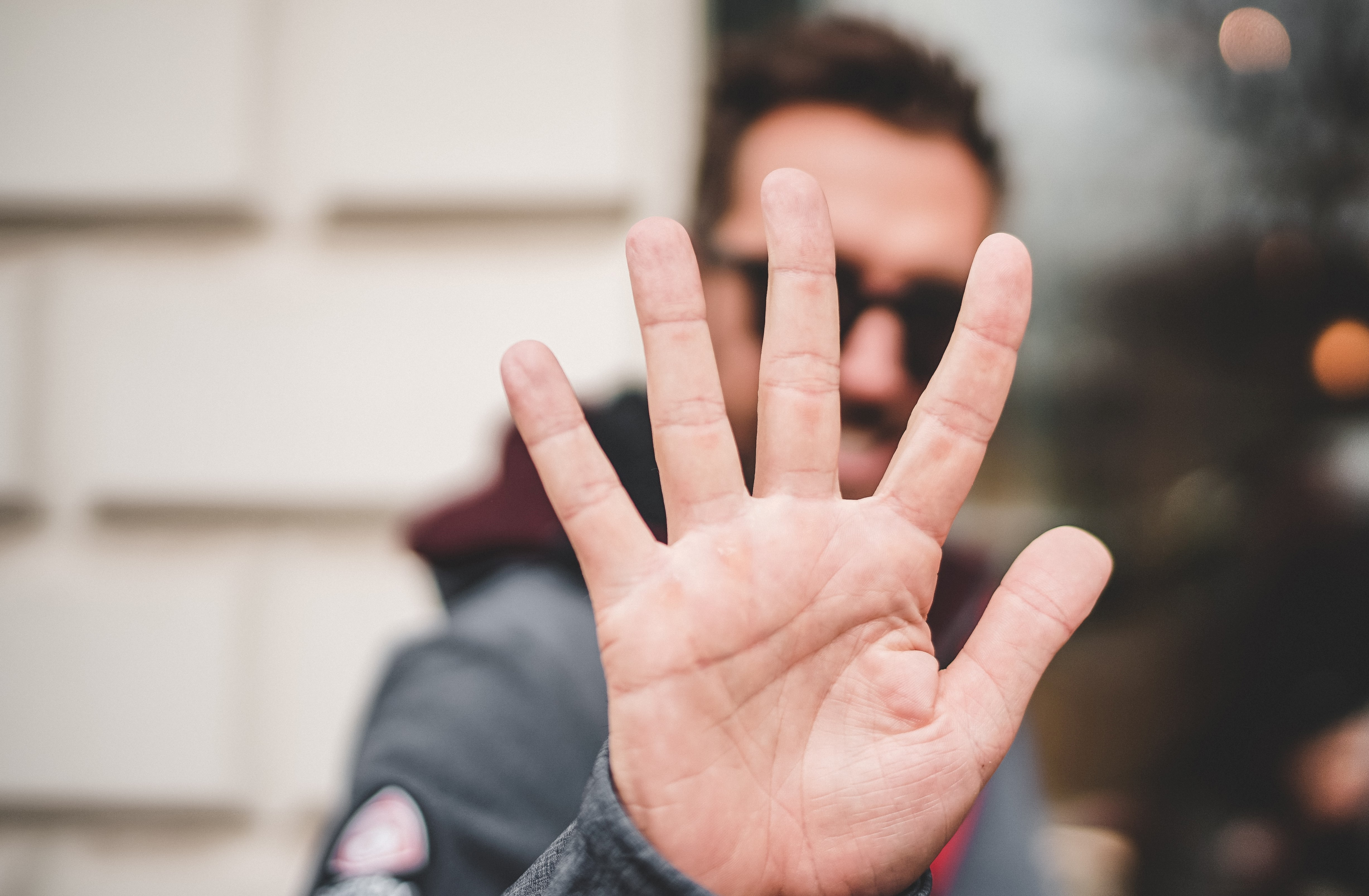 Man holding his hand out to show five fingers.