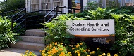 Outside of building with yellow flowers and sign reading: Student Health and Counseling Services