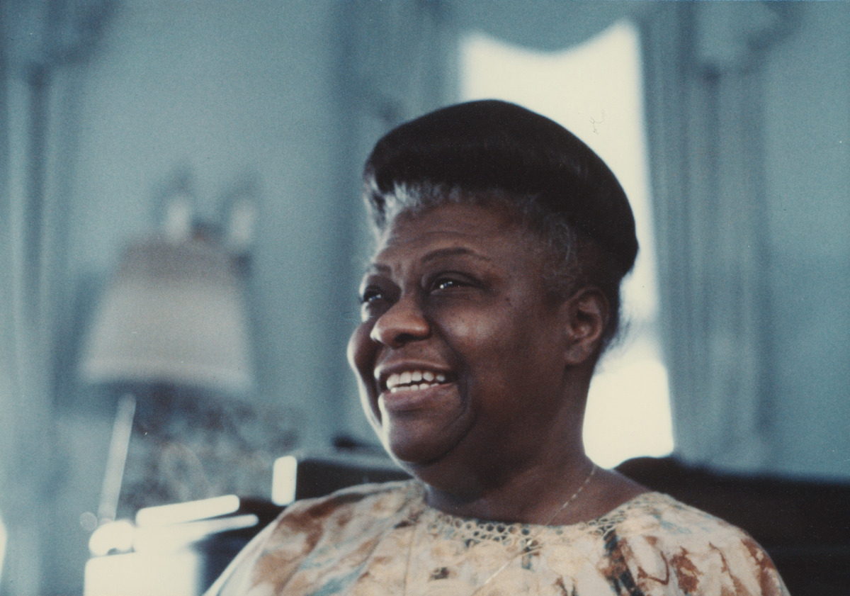 Photo of Elma Lewis smiling. Photo captures Lewis from shoulders up. She is looking off to the left beyond the camera smiling.
