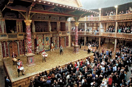 Shakespeare's Globe Theatre interior.  Several actors on the stage and audience members on all three levels.