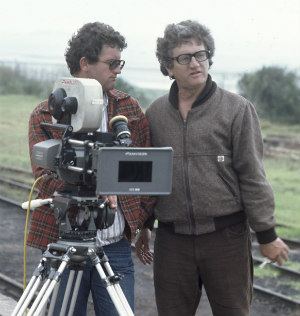 [Tim Burstall with cameraman and one other crew member on train station platform during filming of