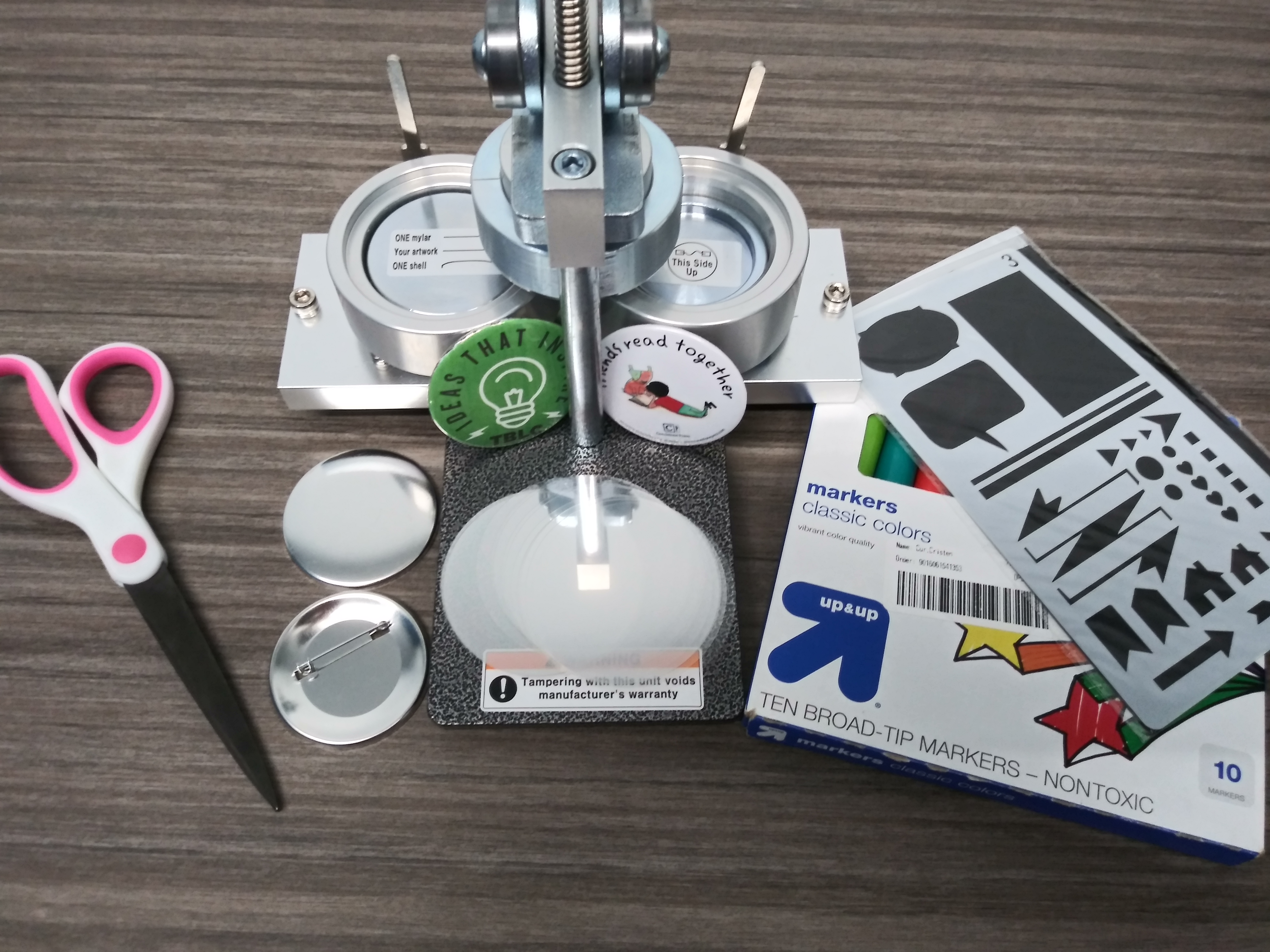 Picture of button maker with accessories including stencils, markers, scissors, and button components