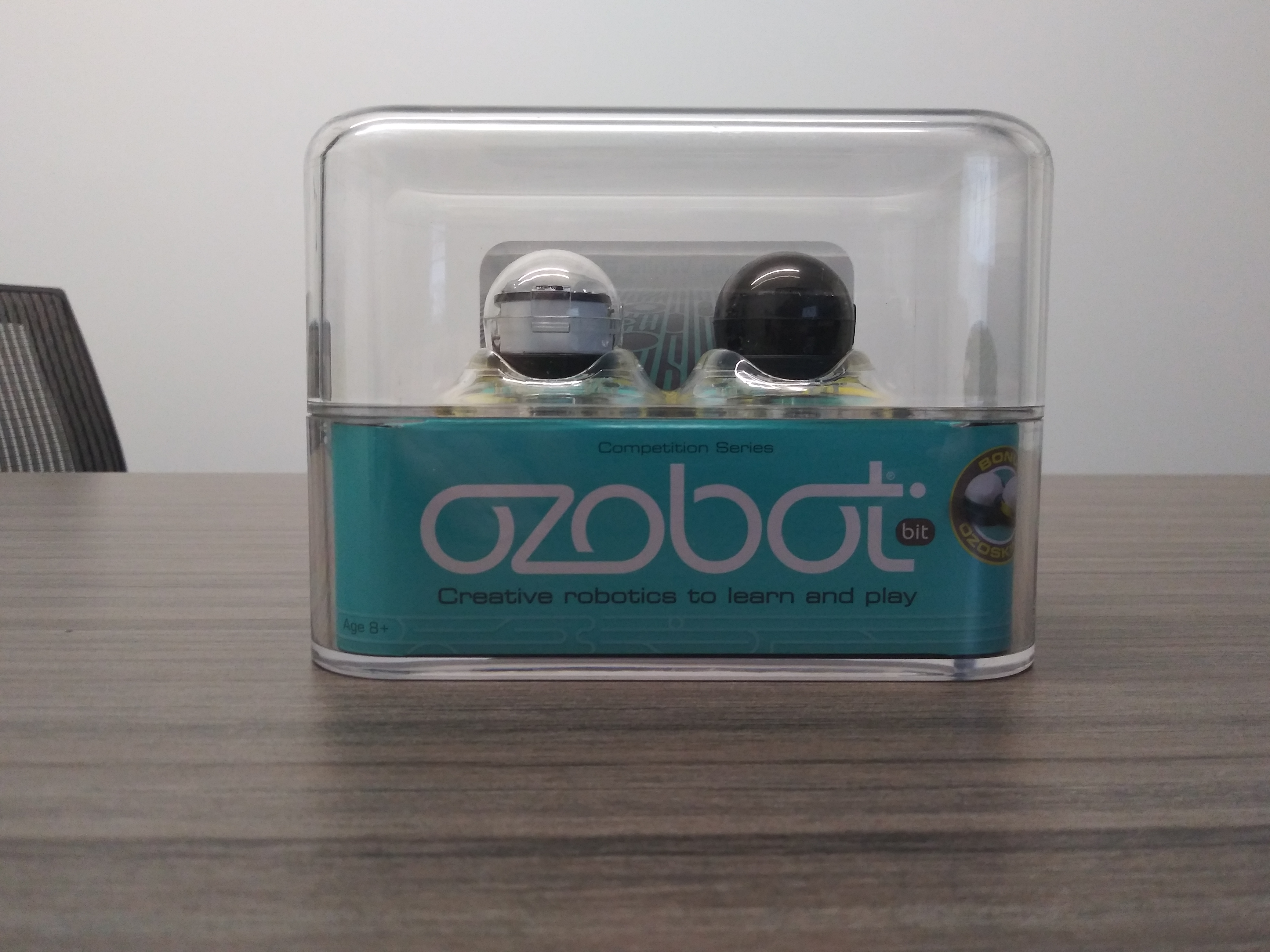 Picture of two Ozobot Bits in packaging - one clear, one black