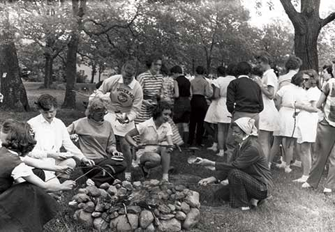 In this ophoto a crowd has gathered around the campfire in order to roast hotdogs at the 1955 field day cookout.