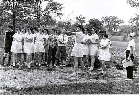 In this photo from a field day held in 1955, 14 onlookers watch an archer.