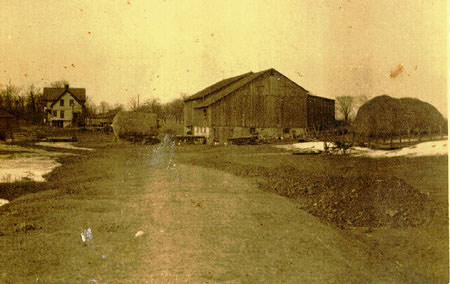 This is a photo of Fisher Farm as it looked prior to the construction of Alverno College. It was purchased by the School sisters of St. Francis in July 1944. In the picture a barn can be seen in the foreground and the white farmhouse that still stands on the Alverno campus is in the background.