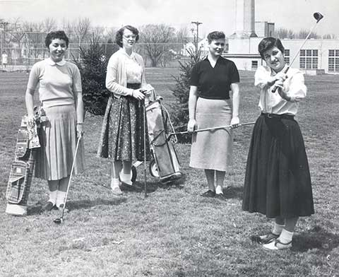 "these four golfers are practicing their swings for a field day held in May 1956. The Powerhouse, the tennis court, and the ""white house"" are in the background."
