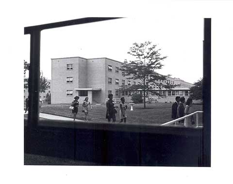 "This photo of the ""North Courtyard"" now known as the ""Alumnae Courtyard"" was taken in the 1960's. In the photo Corona Hall, a tree and a birdbath can be seen in the backyard. In the foreground seven people are strolling through."