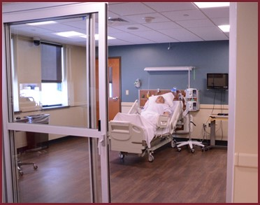This is a color photo of onbe of the nursing simulation rooms found in Alexia Hall. Here is pictured a patient room with a mannequin patient in bed..
