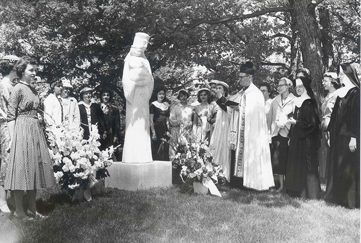"This is a photograph of the 1958 dedication of Sister Helena Steffensmeier's sculpture, ""Mary, Queen of the Universe. At that time the sculpture sat in a grotto in the campus woods."""