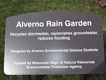"This is a photo of the sign found at the alverno Rain Garden site. It reads: ""Alverno Rain Garden: Recycles stormwater, replenishes groundwater, reduces flooding. Designed by Alverno Environmental Science Students."""